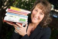 Penny Sansevieri holding stack of books
